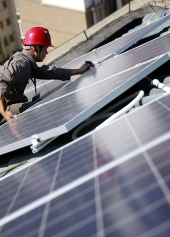 Installing solar panels on a rooftop in Jiujiang, East China